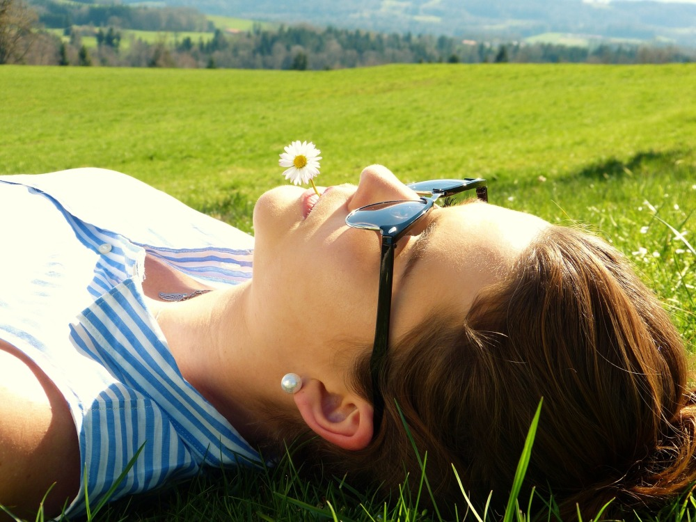 Woman with sunglasses lay in green field with a daisy held in teeth
